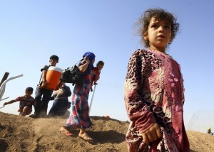 People who fled from the violence in Mosul walk inside the Khazer refugee camp on outskirts of Arbil