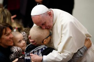 Pope Francis embraces a child as he meets the disabled during his general audience in Paul VI hall at the Vatican Jan. 13. (CNS photo/Paul Haring) See POPE-AUDIENCE-MERCY Jan. 13, 2016.